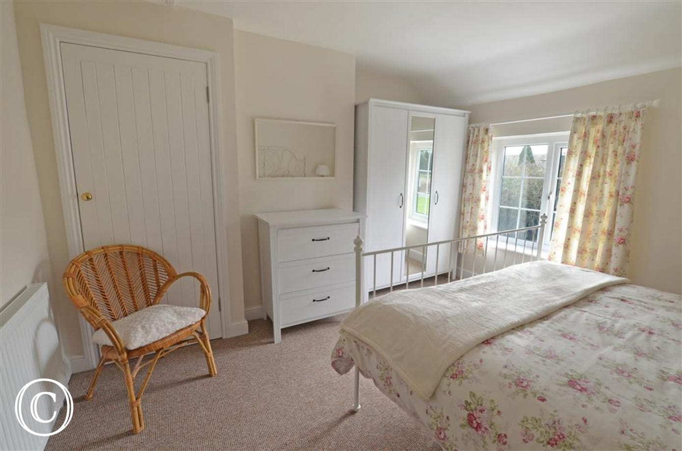 New white bedroom furniture enhances this light filled double room.