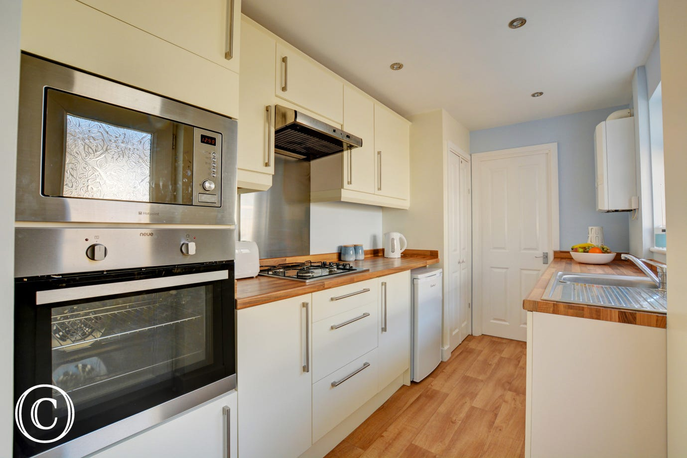 Kitchen with built-in electric oven, gas hob, fridge with icebox, combination microwave and washing machine