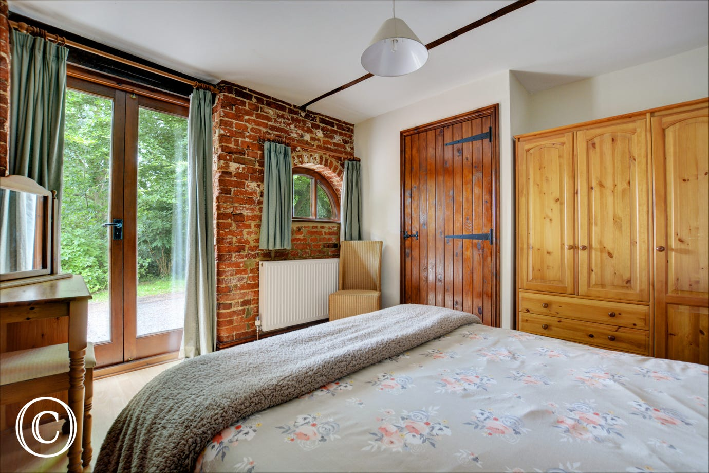 Charming double bedroom with a double bed, French doors and en-suite shower room with shower cubicle