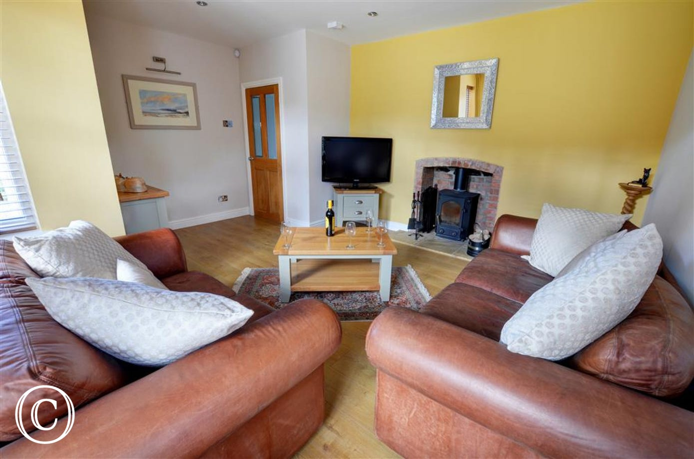 Comfy seating and woodburner in the sitting room