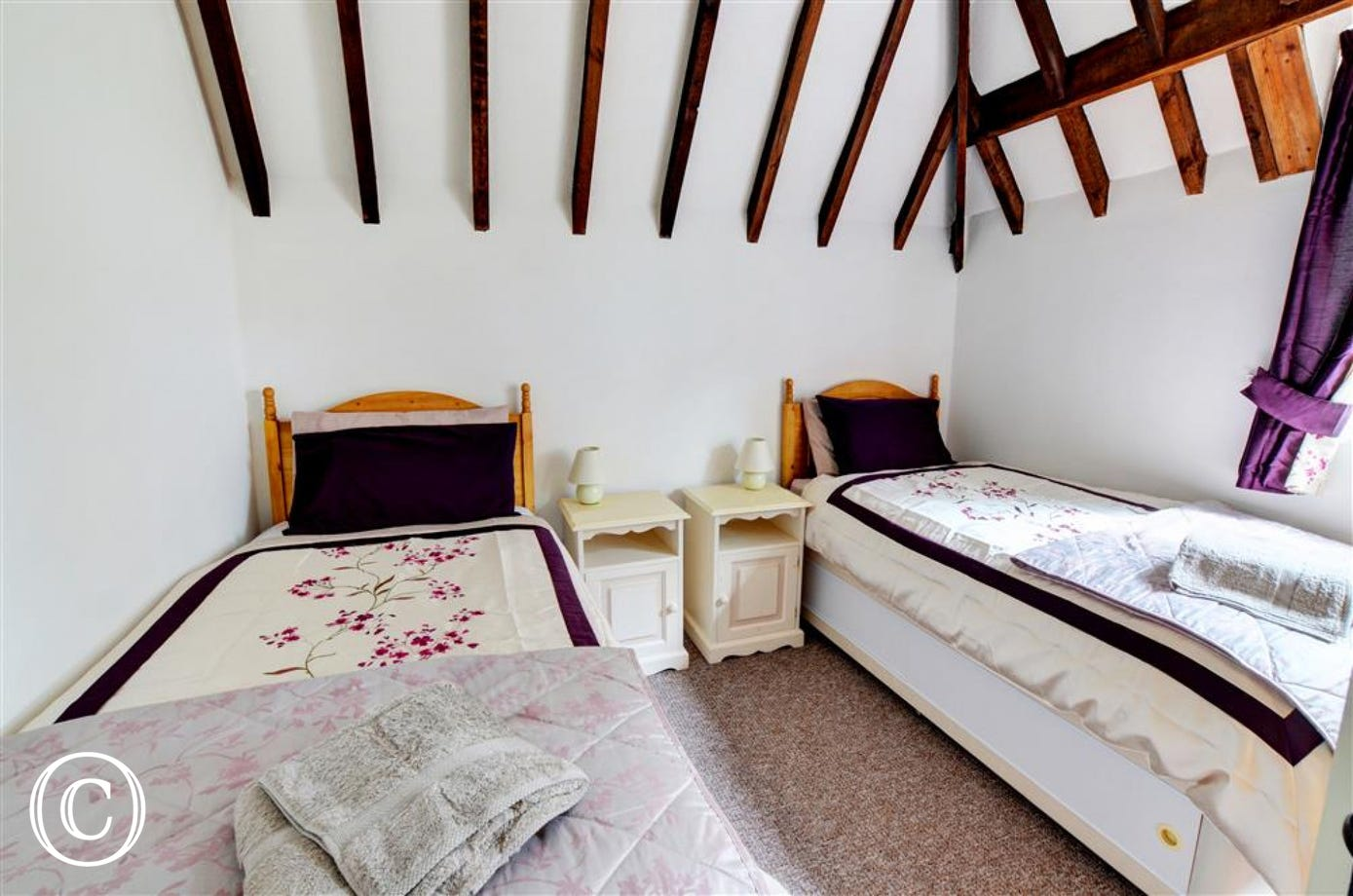 Bedroom two with twin beds and exposed beams