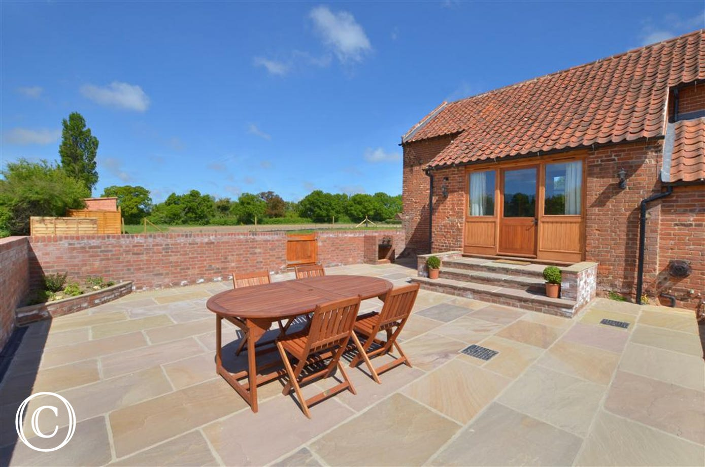 Fully paved, large patio area which is enclosed and has garden furniture and barbecue