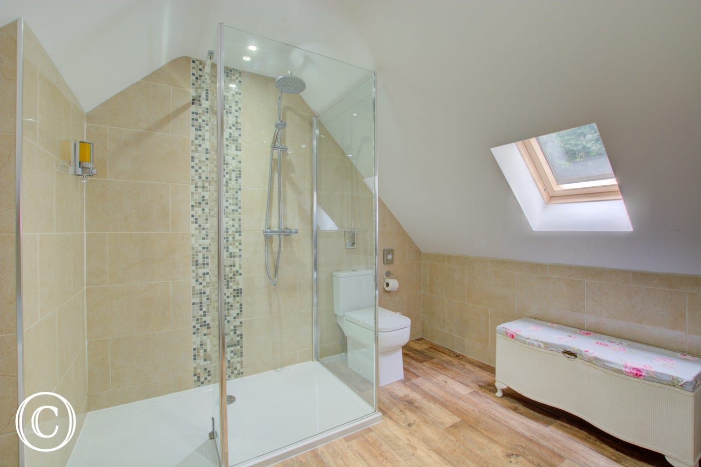 Bathroom has corner bath with waterfall taps and shower cubicle with drench head.