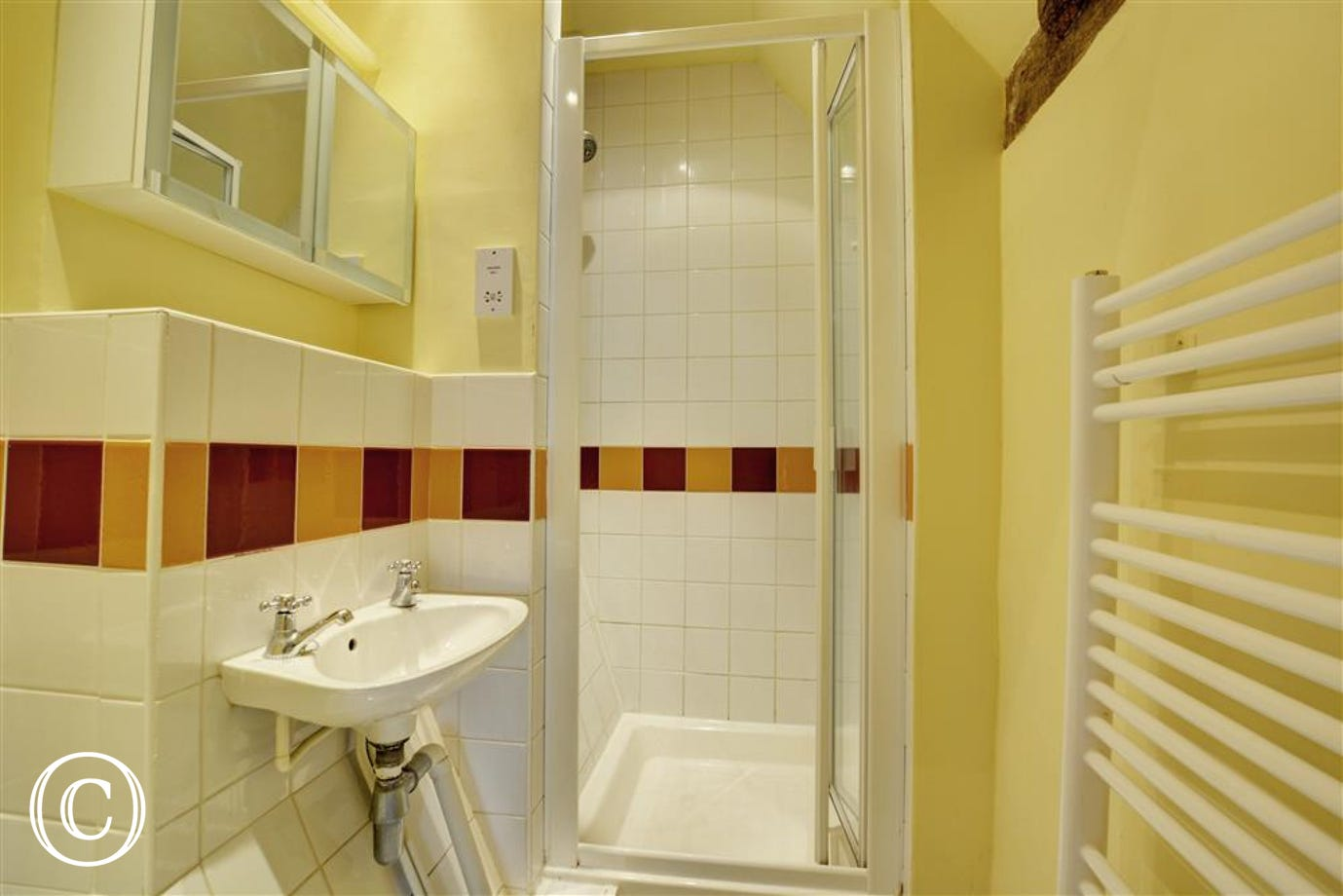 Ensuite shower room with shower cubicle, wash hand basin, and heated towel rail.