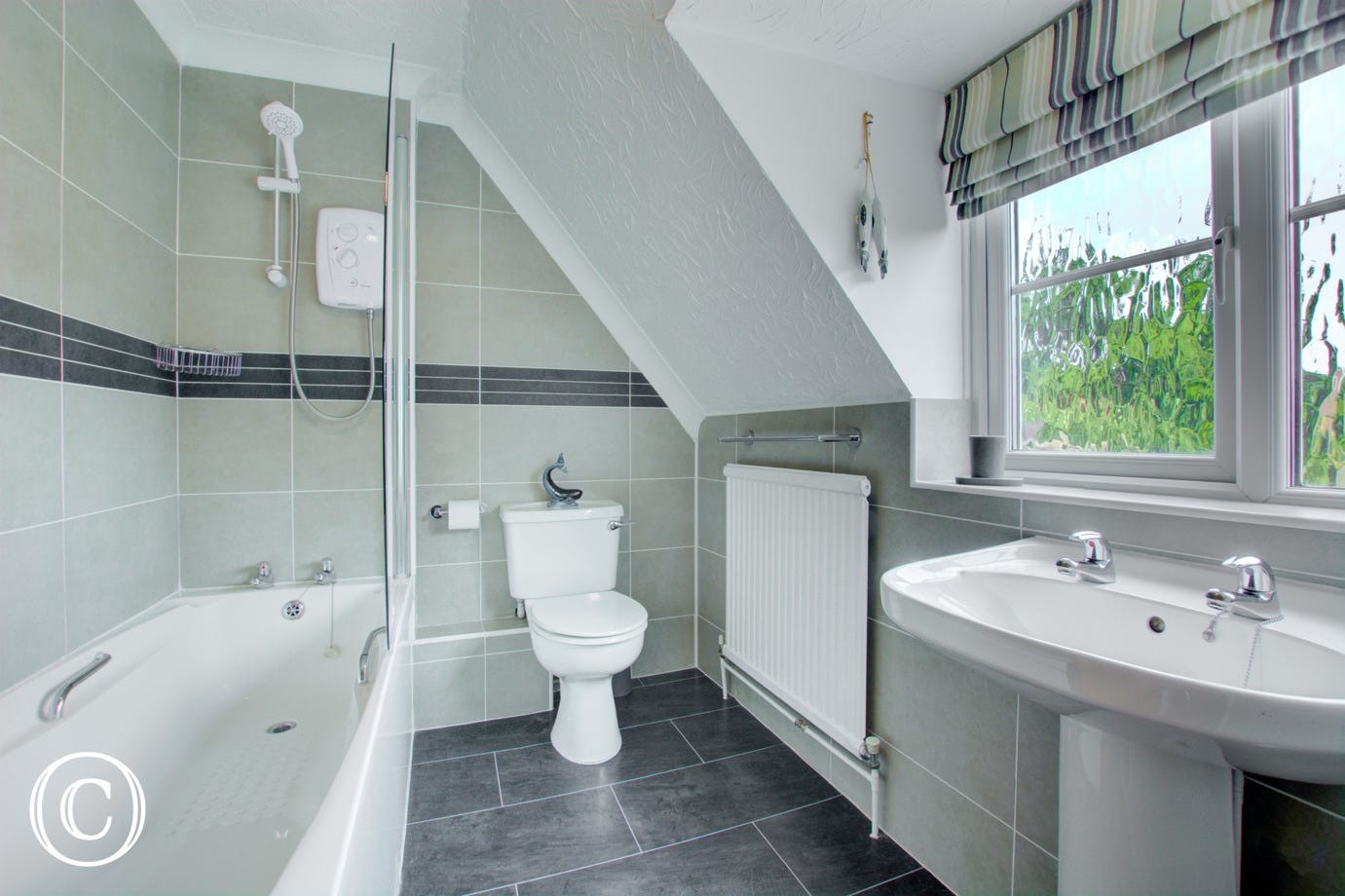 Nicely finished, fully tiled family bathroom with bath, and over bath shower