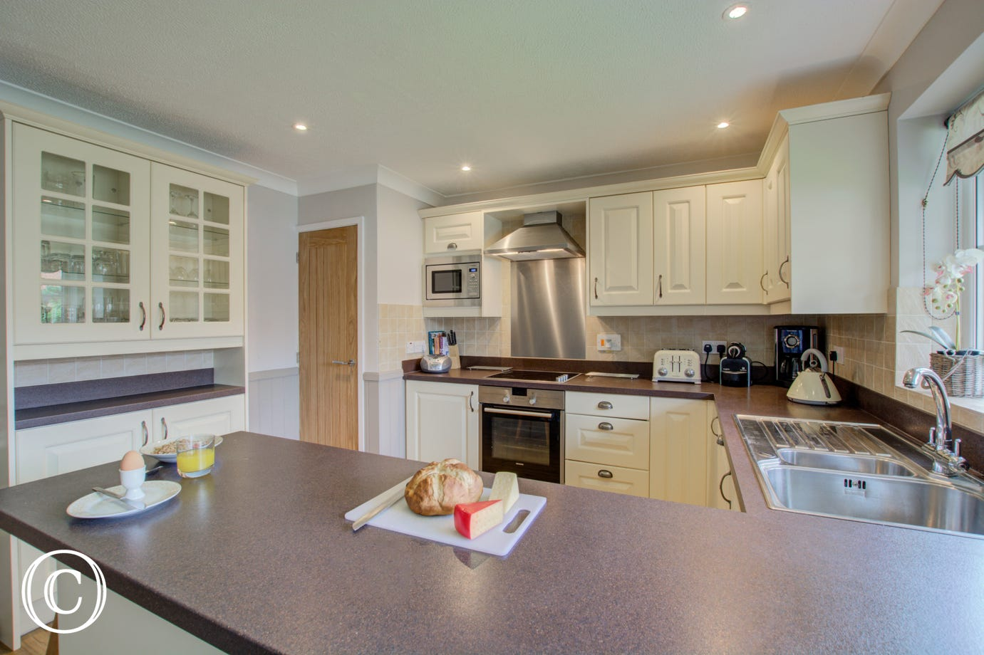 Kitchen with breakfast bar and electric hob and oven.