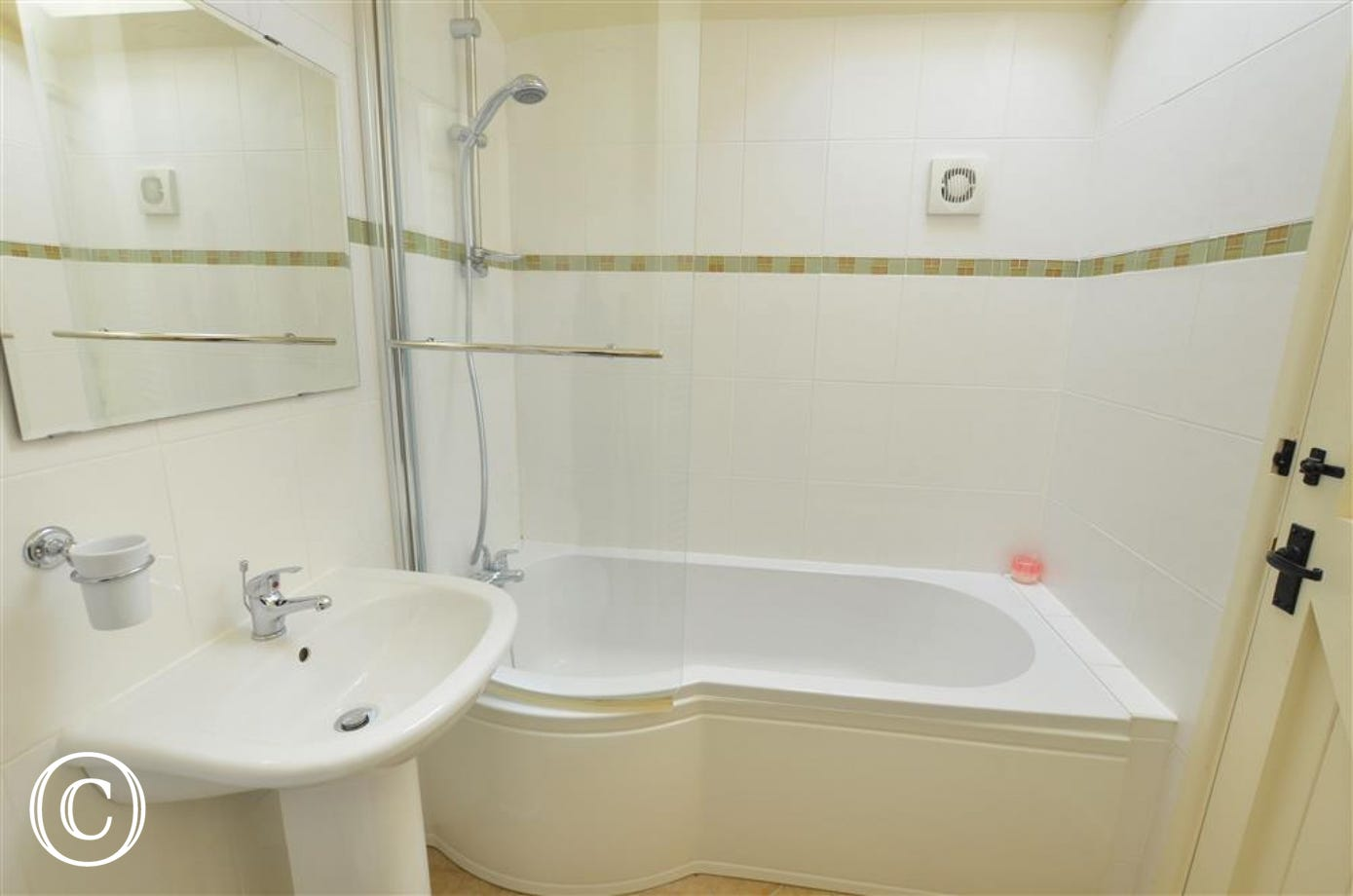 En suite bathroom with bath and over bath shower