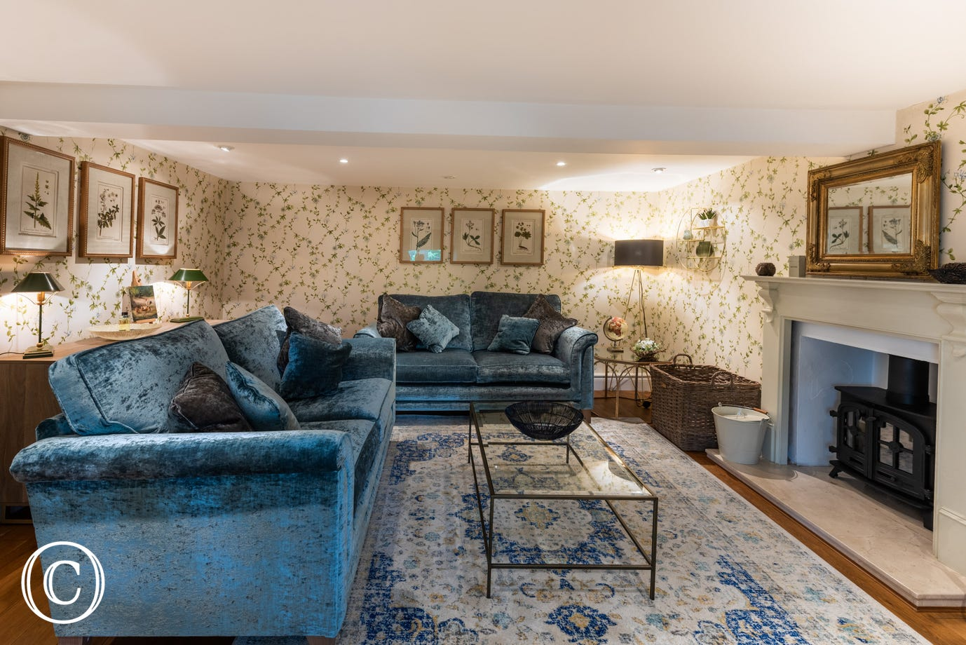 Large sitting room with comfortable seating and a woodburner