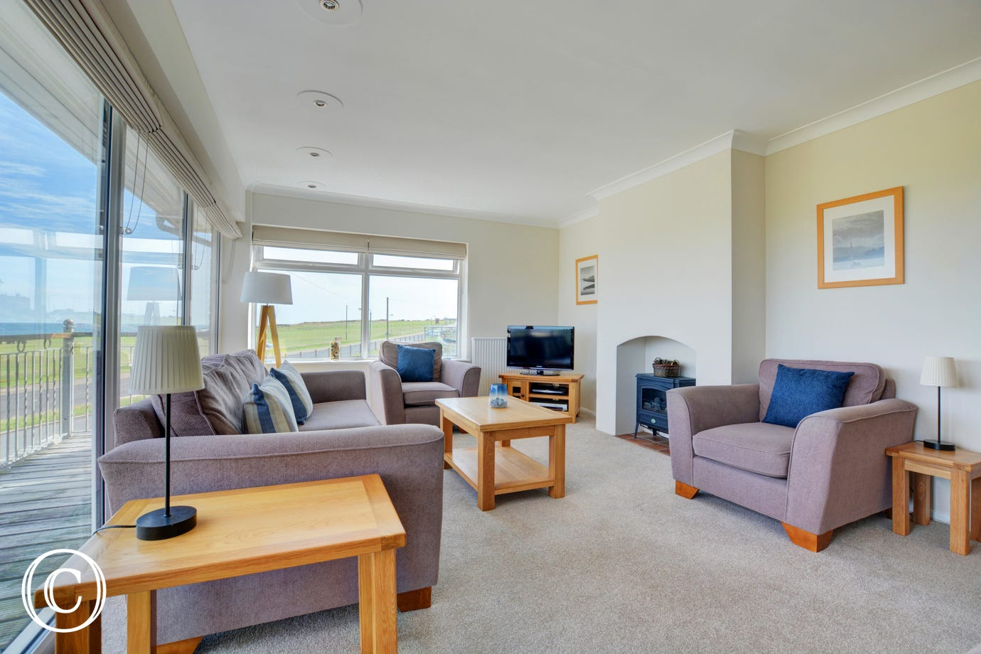First floor pleasantly furnished with comfortable seating, electric woodburner-style fire and door to the balcony with splendid sea views