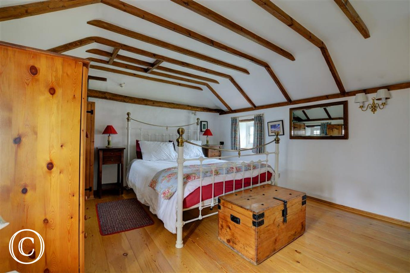 Cottage style bedroom with trunk at the foot of the bed and pine wardrobes.