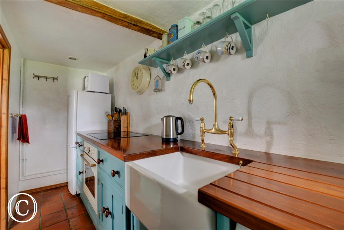 Small galley kitchen with cottage styed kitchen cupboards, wooden work surfaces and butler styled sink.