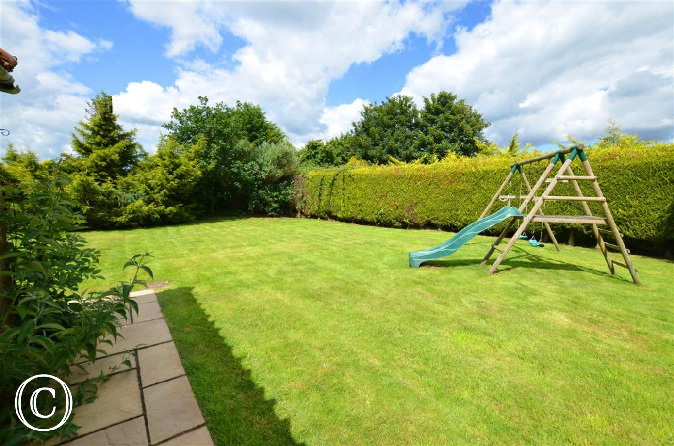 Large lawned area with climbing frame and slide