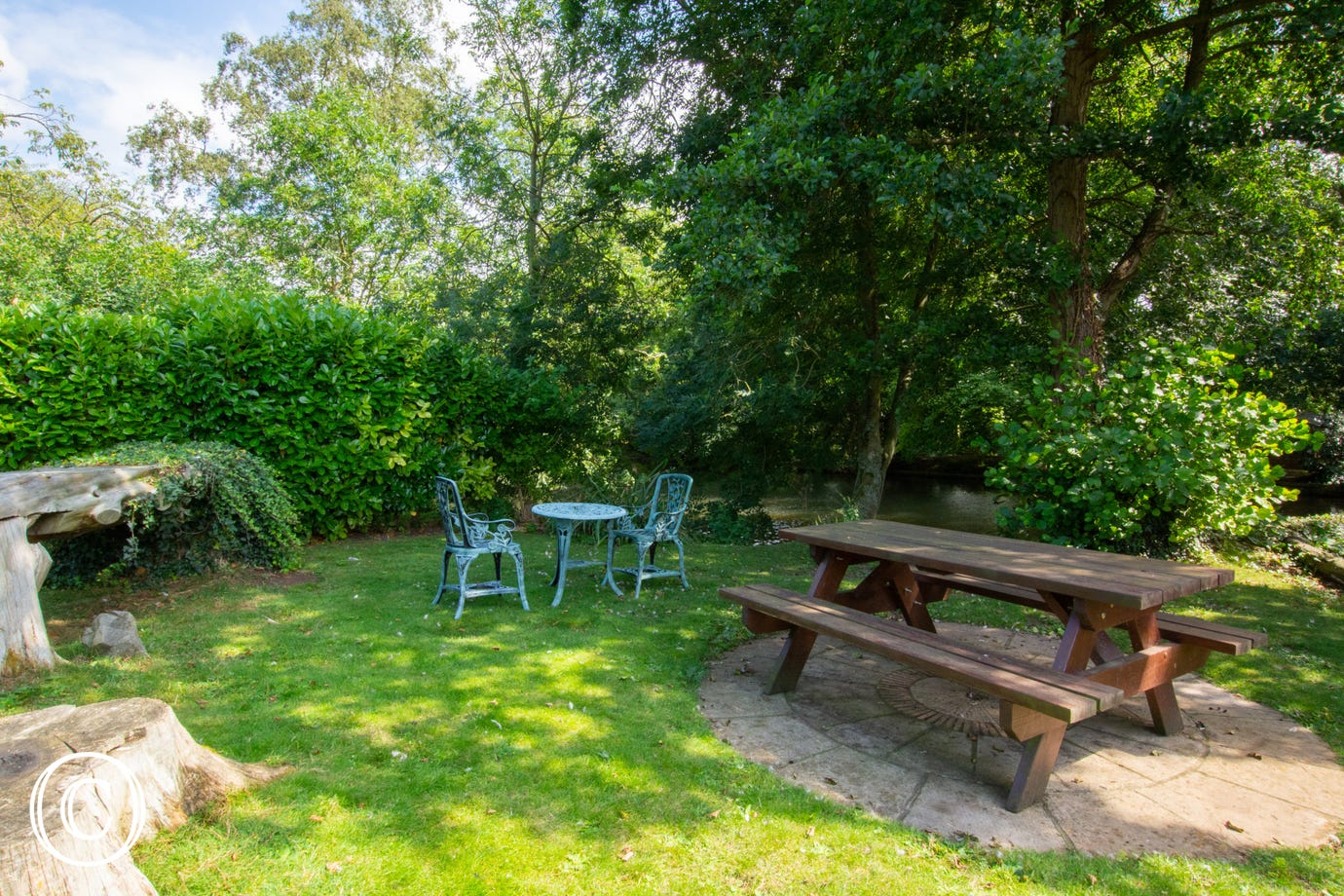 Patio with picnic table in pretty wooded area.