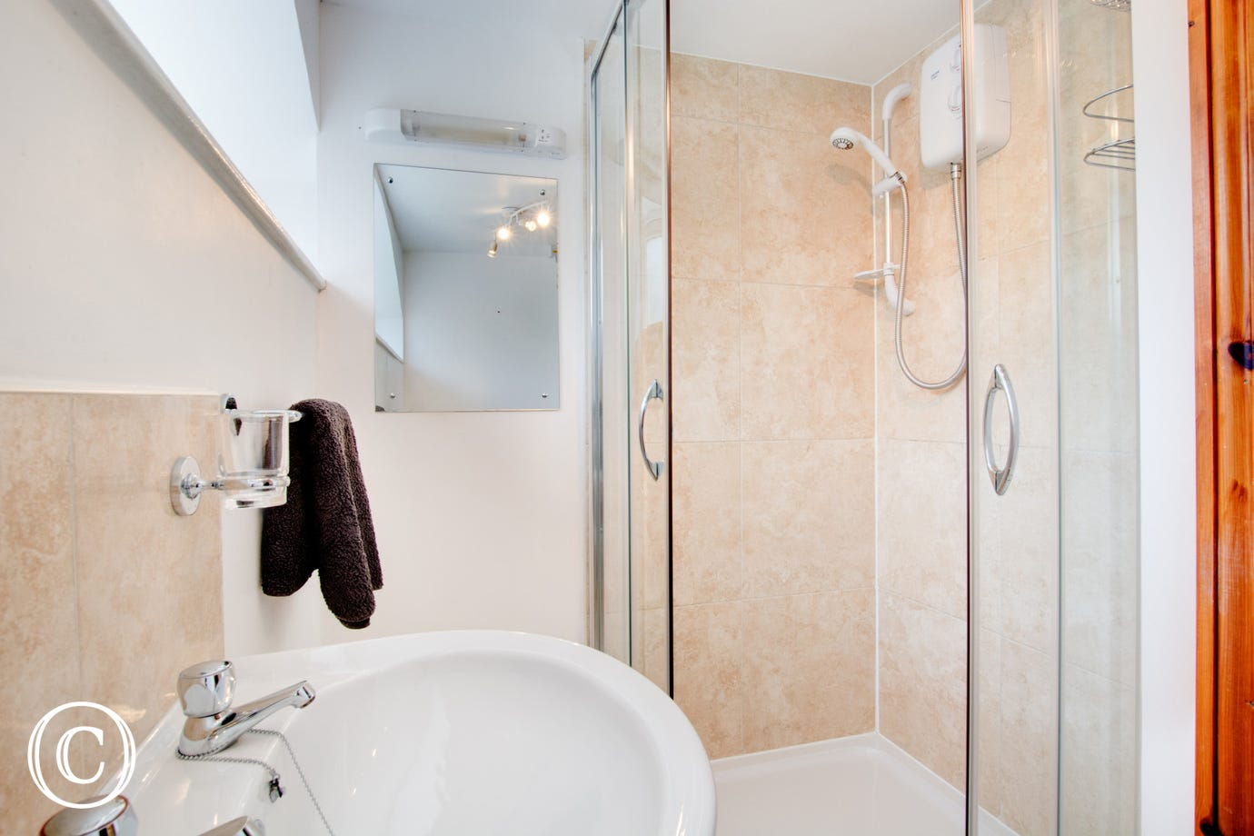 Compact ensuite showing shower cubicle and basin.