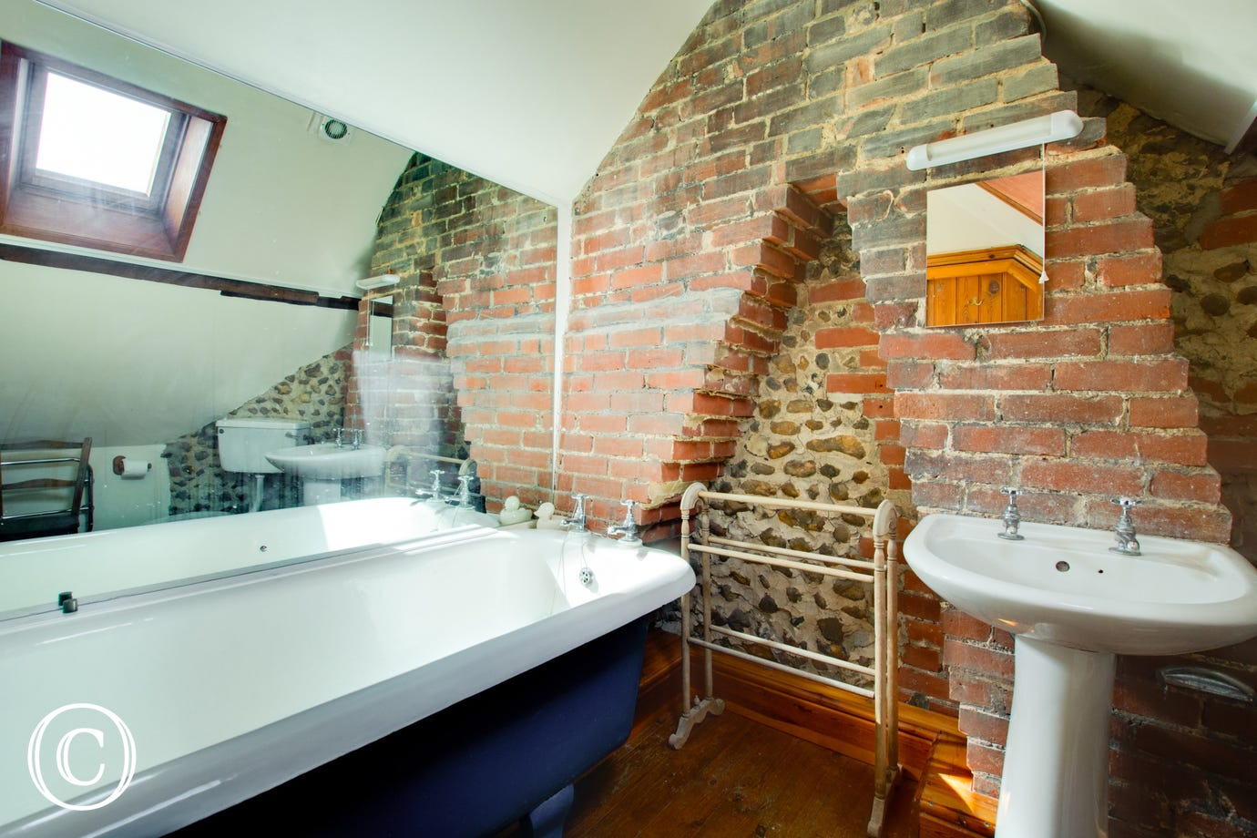 Beautiful en-suite bathroom with a roll-top bath and exposed brickwork