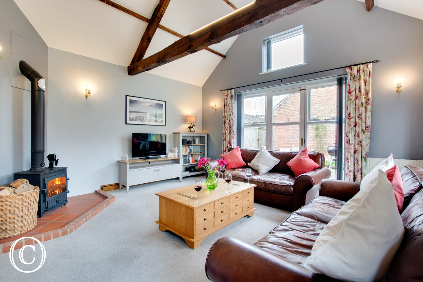Spacious open plan sitting room with TV, access outside and cosy woodburner
