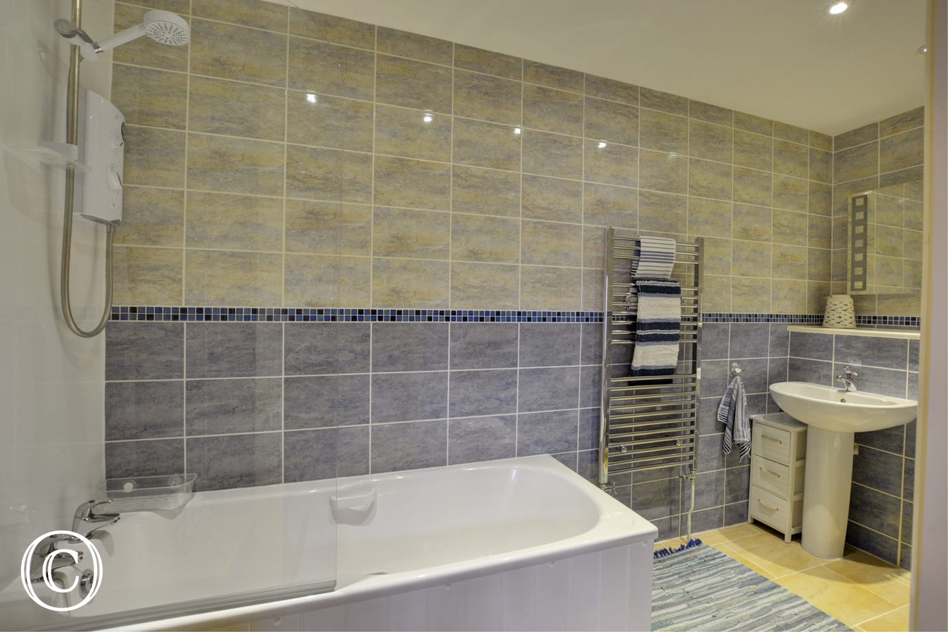 Bathroom with bath with shower over, washbasin and wc