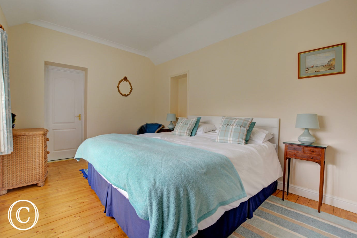 Spacious double bedroom with crisp white bed linen, and pretty pale turqoise throw and cushions.