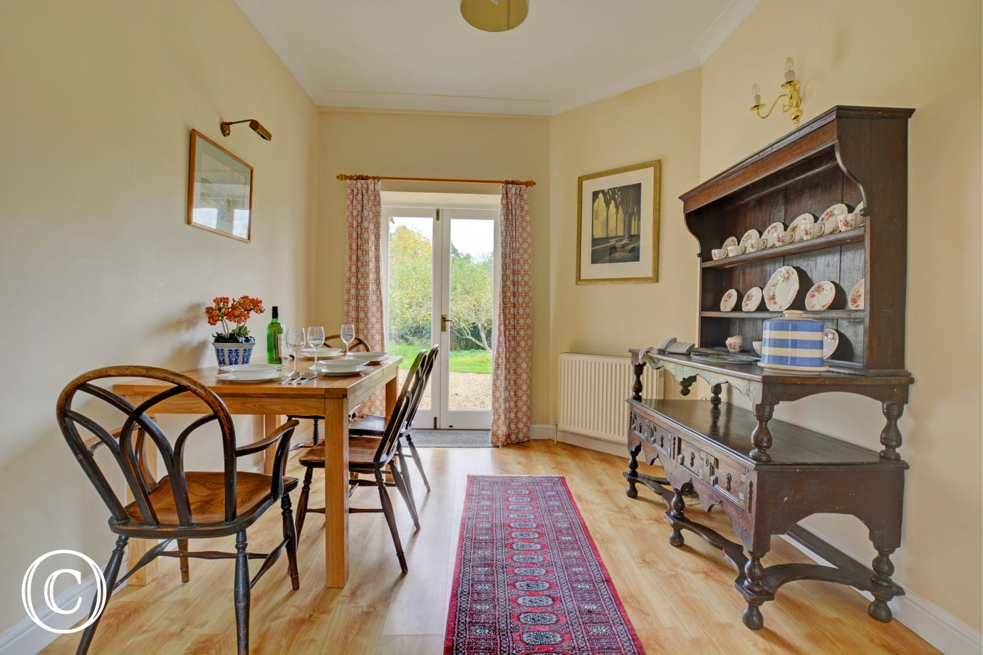 Dining room with doors leading out to the garden,  furnishings of a dark wood dresser and ding table and chairs.