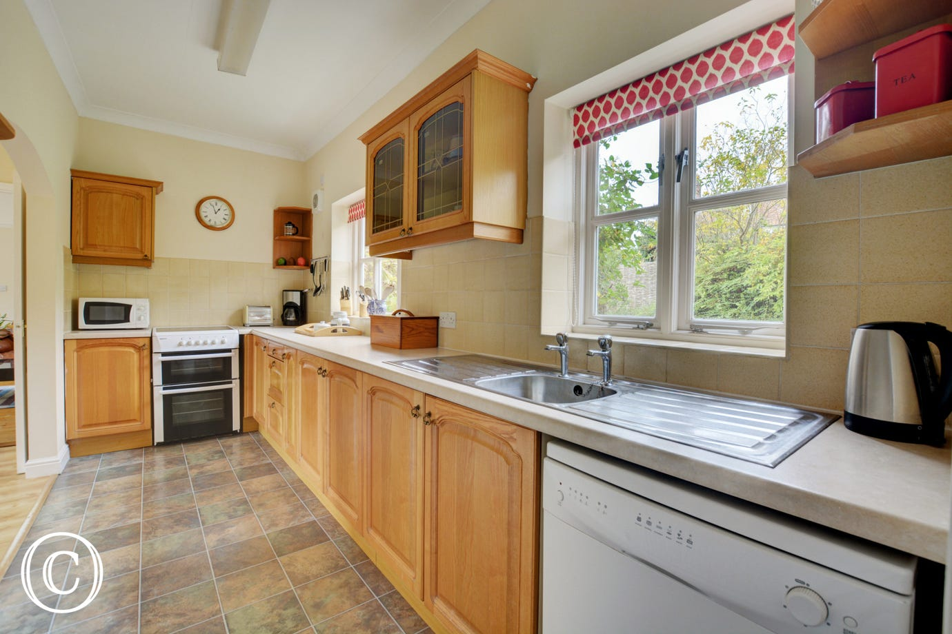 Light wood kitchen units with window facing into garden.