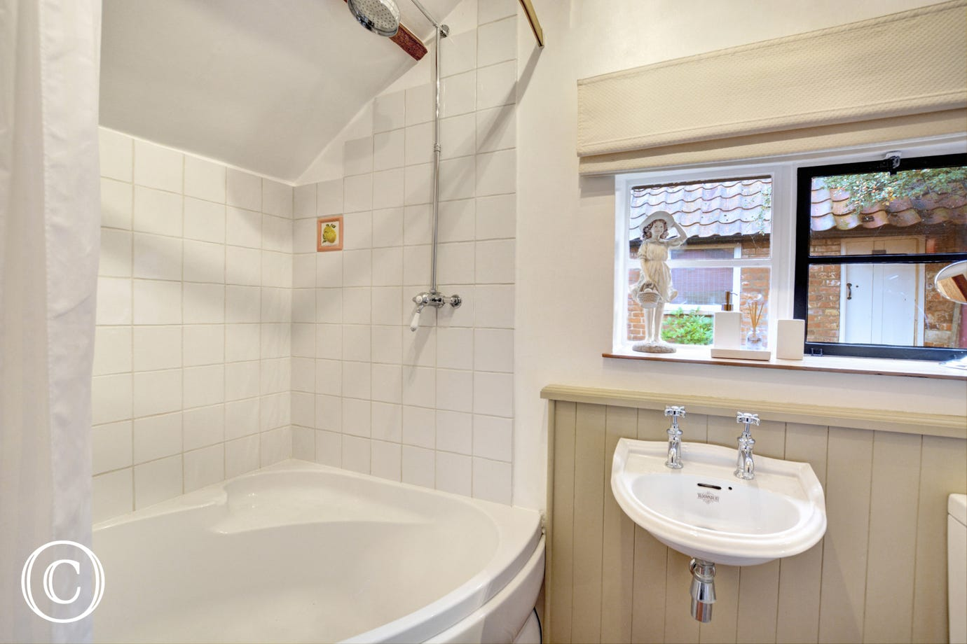 Bathroom with large corner bath, over-bath shower with rainfall shower head, washbasin and wc