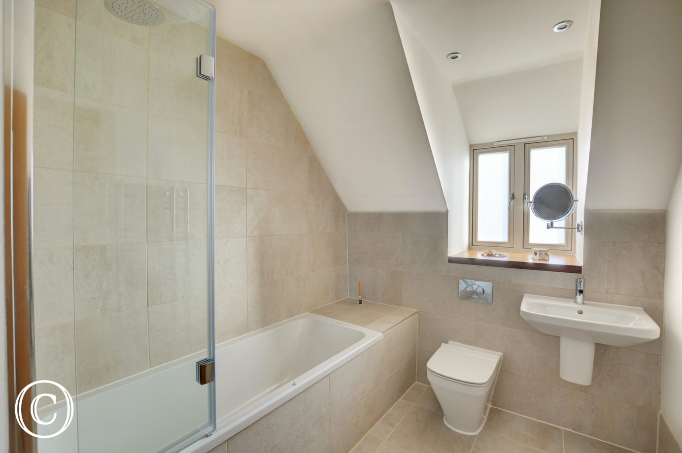 Bathroom with over the bath shower, washbasin and w.c