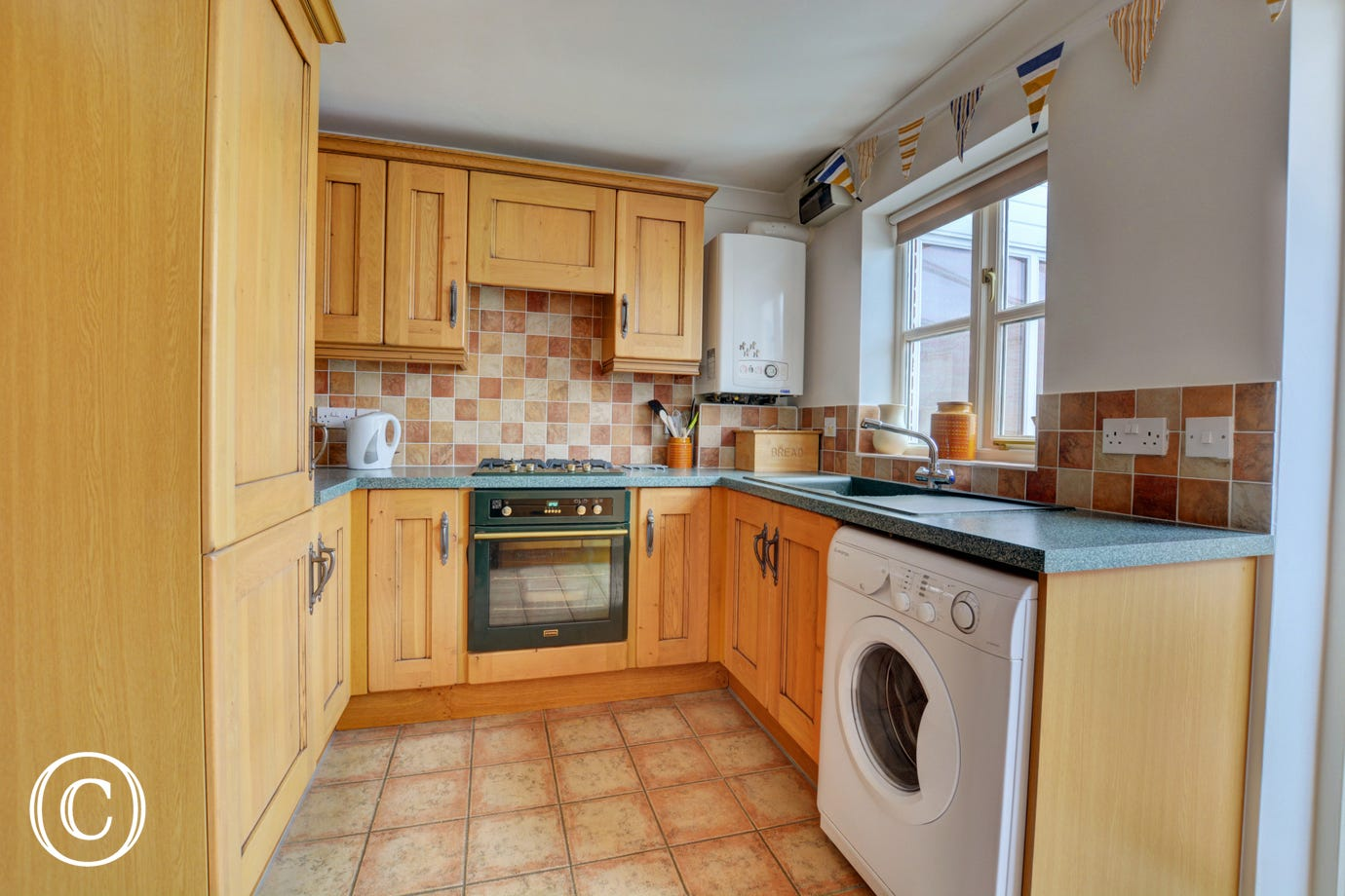 Kitchen with electric oven, gas hob, microwave, fridge/freezer and washer/dryer