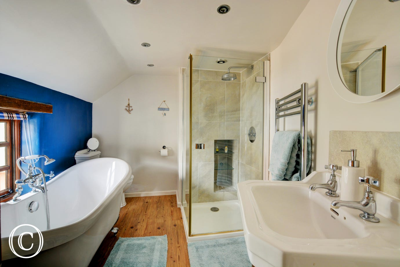 En -suite bathroom with roll top bath, shower cubicle, washbasin and w.c