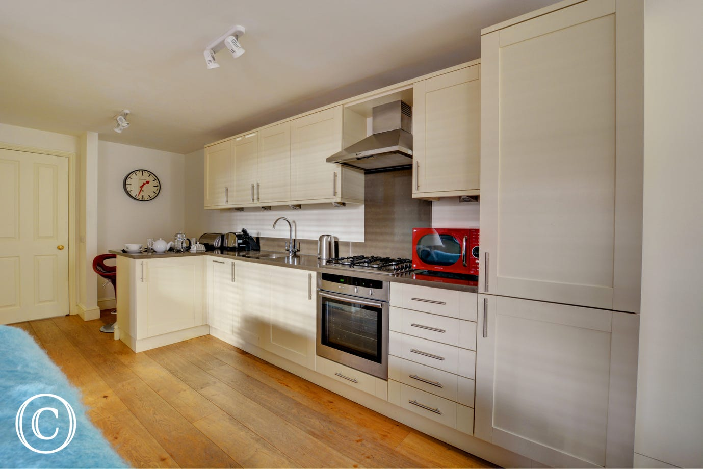 Modern kitchen area with gas hob and electric oven.