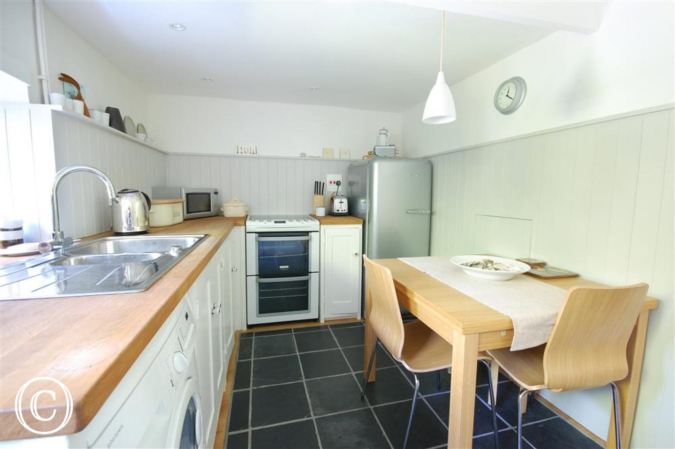 Modern and contemporary kitchen with most major appliances, well equipped and a table, chairs and stools, ideal for family meals
