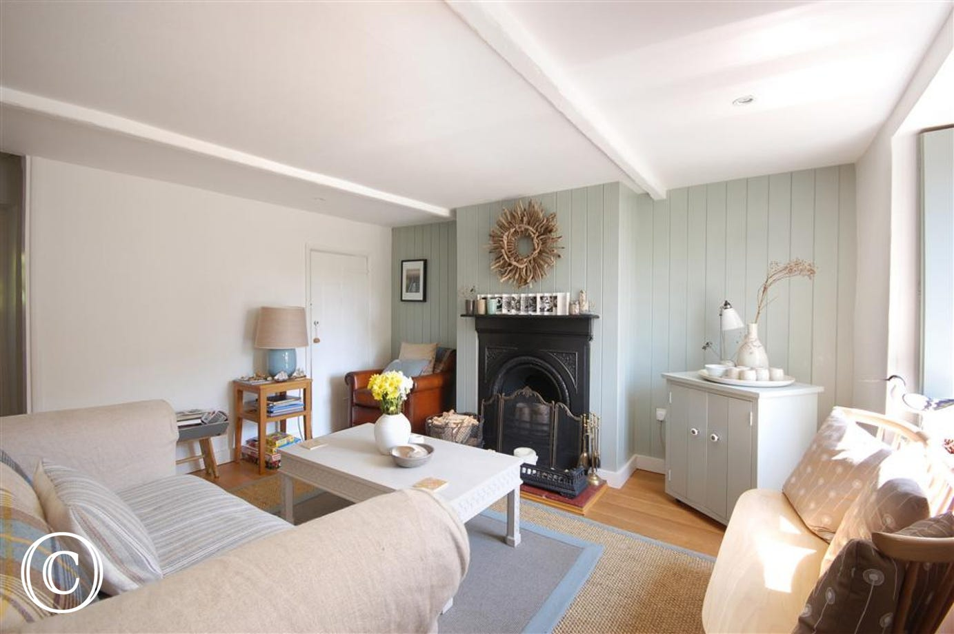 The bright sitting room is stylishly furnished with comfortable seating and an open fire for cosy evenings