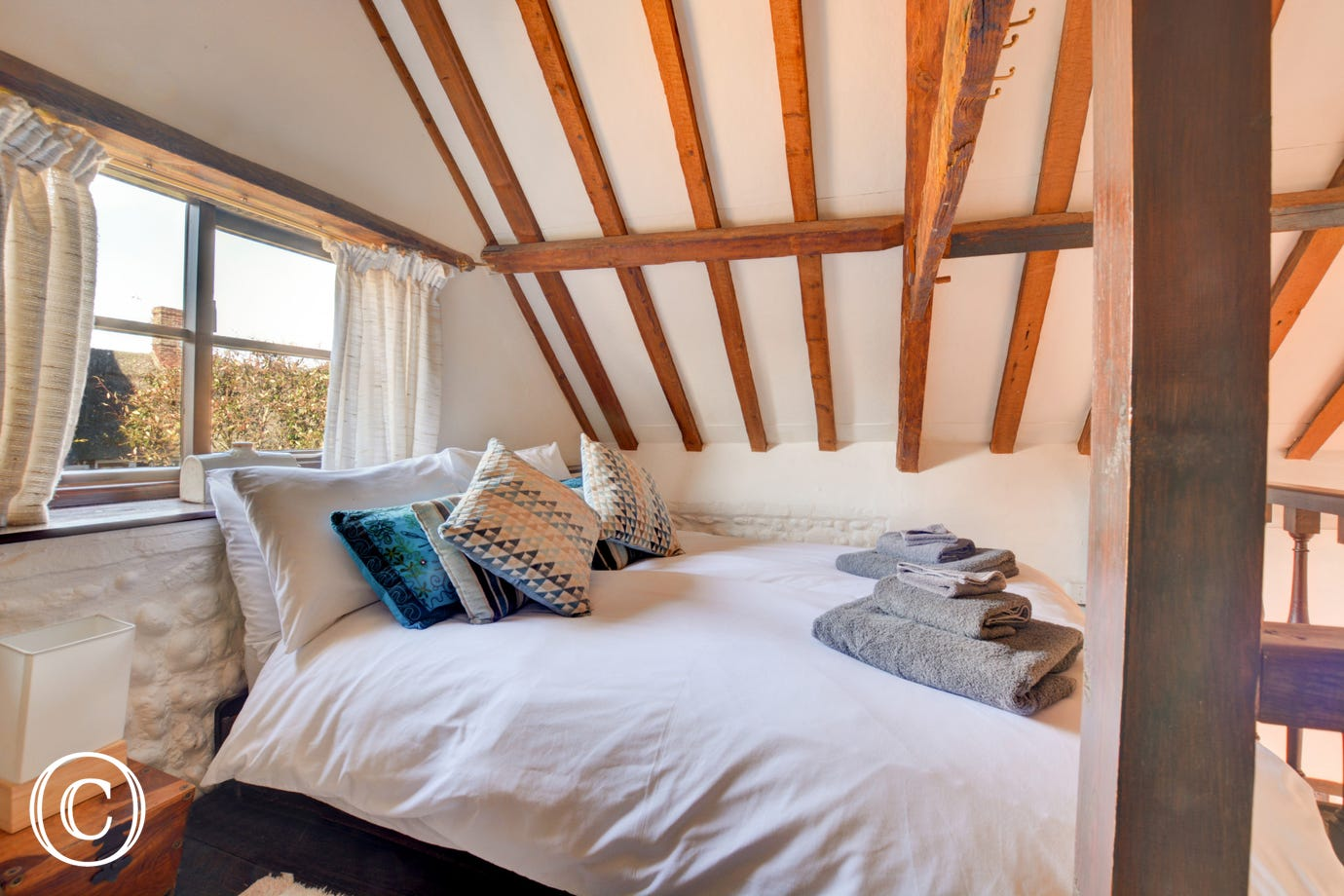 Characterful gallieried double bedroom which can be accessed from the dining area, steep wooden steps which can be left in position or put into vertical position to give more space below and a double low-level bed, drawers and hanging space.