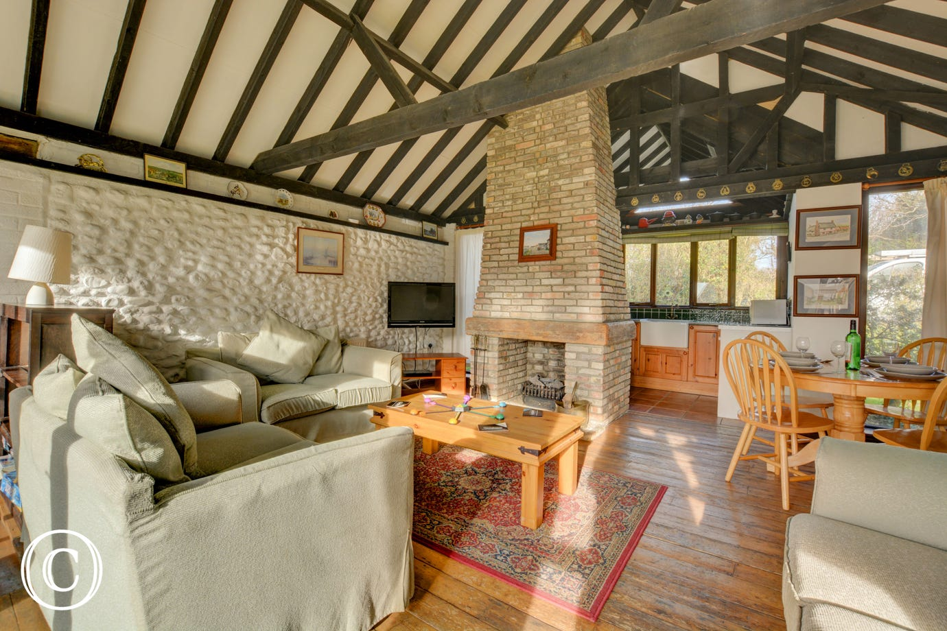 The spacious sitting/dining area has comfortable seating, and a Tudor brick fireplace with a gas log fire for cosy evenings