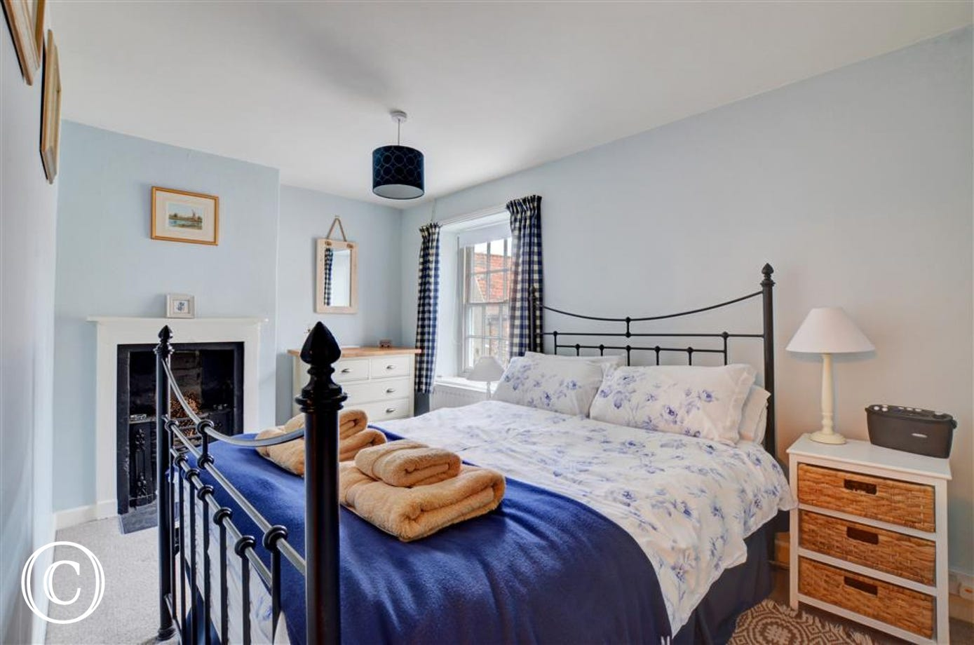 Beautiful double bedroom in blues and white, with wrought iron bed and feature fire place.
