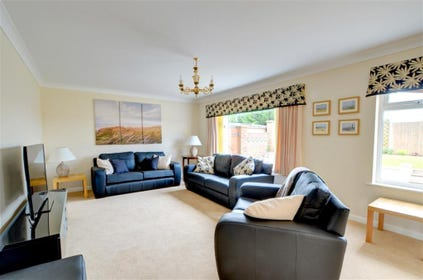 Comfortably spacious sitting room, with leather sofas and flat screen TV.