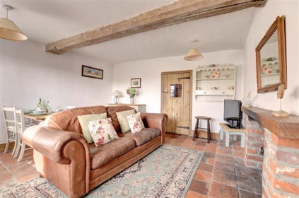 Lovely cosy sitting room with rustic open beams and multi fuel stove