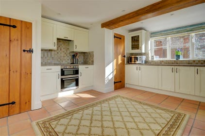 The kitchen is a spacious room with an electric cooker and a dining area