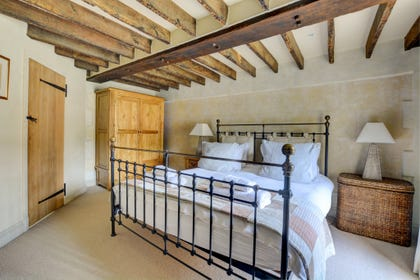 The main bedroom has stunning open beams and bare brick features.