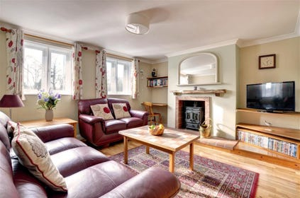 Cottage styled sitting room woth sofas, coffee table, Flat screen TV and wood burner in fireplace