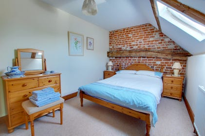 Charming double bedroom with exposed brickwork and a velux window