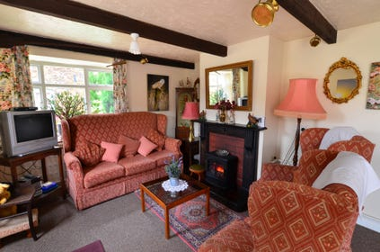 Open plan sitting area with comfortable seating, feature fireplace and characterful beams