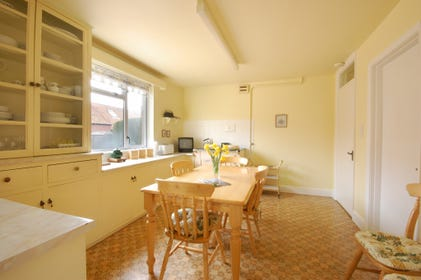 There is a dining table and chairs at one end of the kitchen, ideal for family meals