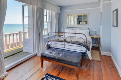 A double bedded room with double doors onto the verandah, overlooking the bay of Cromer.