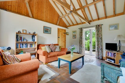 The sitting room attractively furnished with comfortable seating, TV, Freeview, video, woodburner and French doors leading to the patio garden.