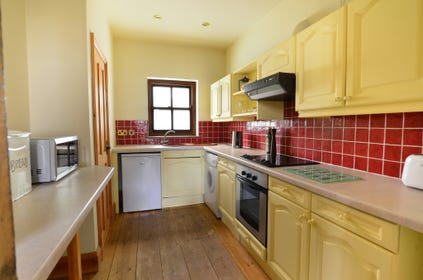 A galley kitchen with electric cooker, fridge, microwave and washing machine.
