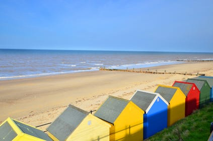 A view of Mundesley beach with colourful beach huts