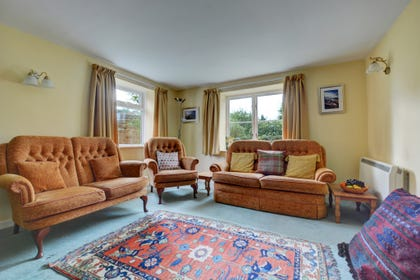 The open plan sitting room has been furnished traditionally in a cottage style