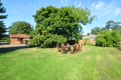 Shared open-plan lawned area with garden furniture and barbecue, ideal for al fresco dining