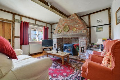 The sitting room is attractively furnished with comfortable seating, a lovely inglenook fireplace with an electric woodburner-style fire and beamed ceilings