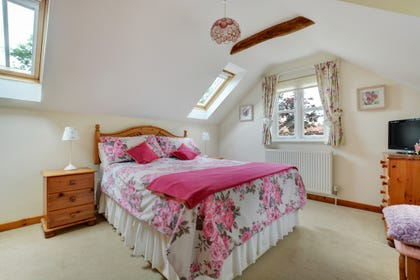 Double bedroom with a double bed, sloping ceiling and tasteful furnishings
